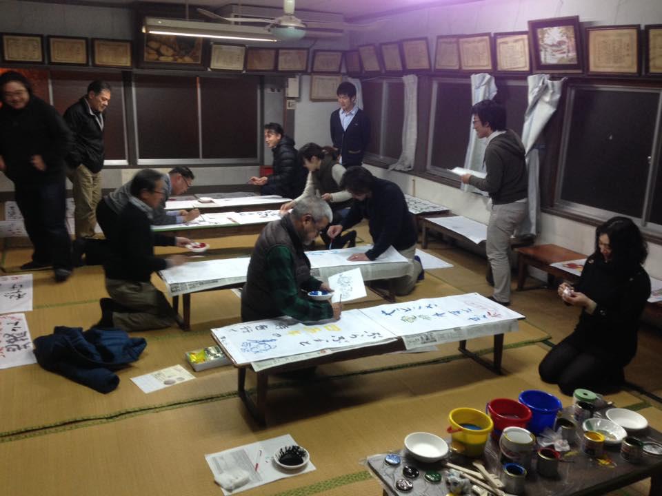 ▲商店街の人々が唐人町会館に集まりタペストリー制作。  画家の大歯雄司さん、大串亮平さんも協力。