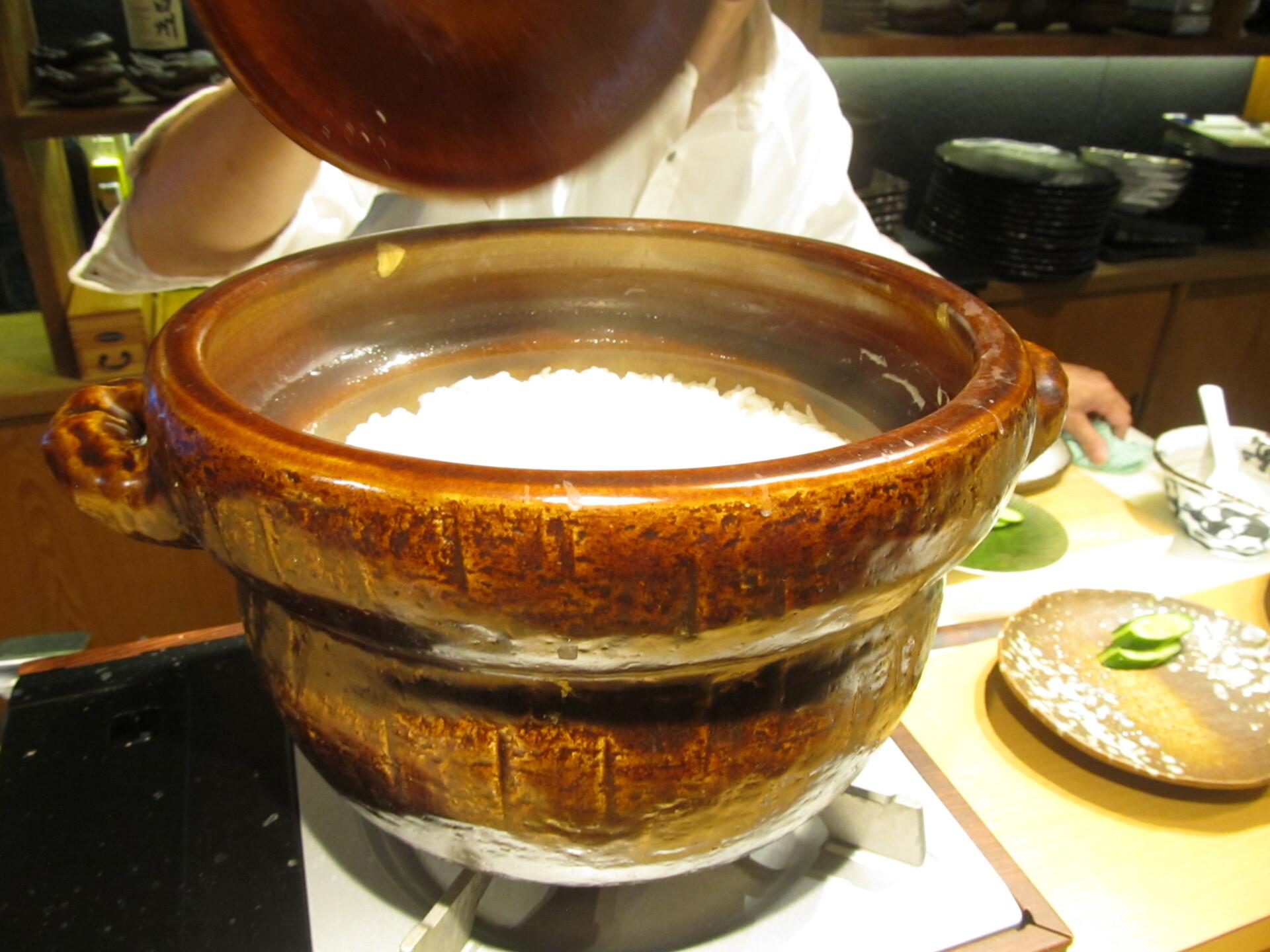 土鍋から湯気がこぼれる炊きたての白飯